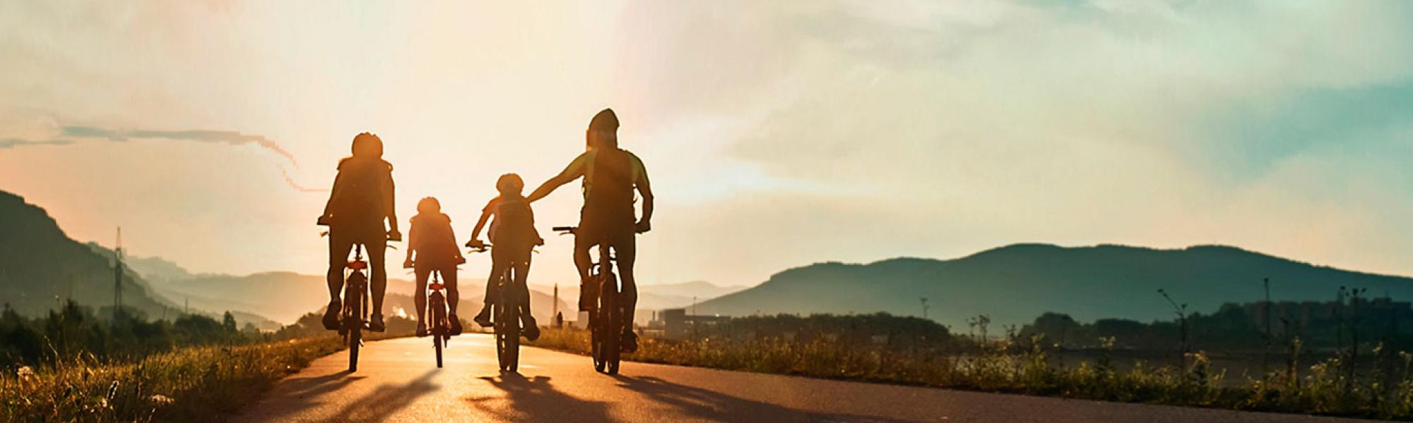 family riding bikes into sunset
